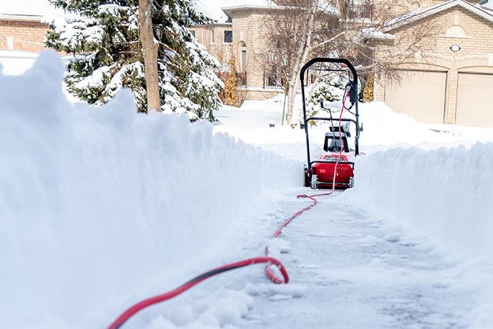 Electric snowblower in distance with extension cord